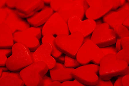 Lots of red hearts as a background. The concept of St. Valentines Day, love, sweets