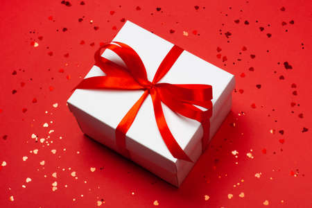 Trendy attractive minimalistic gift on the red background with hearts. Merry Christmas, St. Valentines Day, Happy Birthday and other holidays concept. Stock Photo