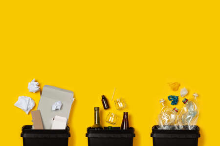 Paper, glass, plastic in black containers on a yellow background. The concept of separate collection of waste, sorting of waste, recycle, informed consumption. Flat lay. Copy space. Stock Photo