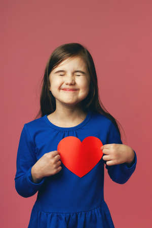Funny little girl delighted with received valentines. Blue dress and red heart. Valentines day concept, love for all ages.