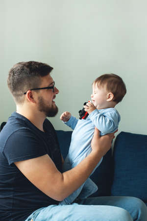 Dad is playing with his son. The baby is laughing. The concept of communication between dads and children, entertainment in quarantine, stay at home.