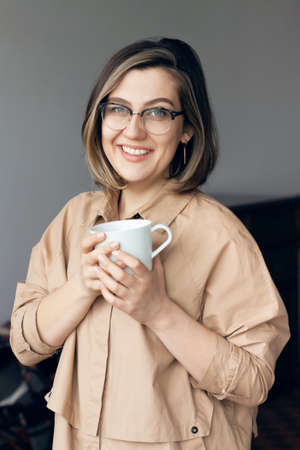 Portrait of stylish intellectual credible woman. Nice smile, glasses, cup of tea in hands. The concept of a doctor, psychologist, psychiatrist, blogger, designer.