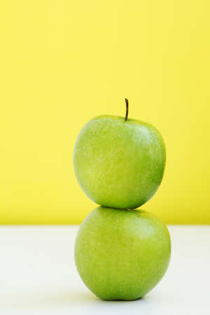 Green ripe apple on the apple on the yellow background