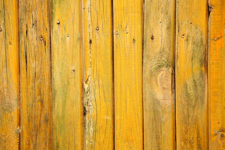 Old wood background with shabby yellow paint. Vintage texture of the wooden wall.