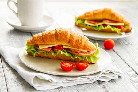 due deliziosi croissant panino con pomodori e insalata sul tavolo in legno grigio, sana colazione in un caffè Archivio Fotografico
