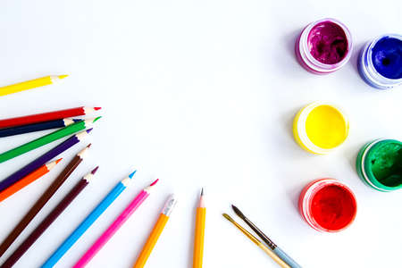set of plastic cans with colored paints, brushes, pencils on white background. Drawing tool. Top view