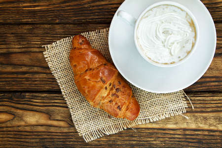 white cup of hot coffee with whipped cream and a croissant on a dark wooden table