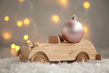 wooden car with pink Christmass ball on a wooden gray background and lights from the garland. Christmas card