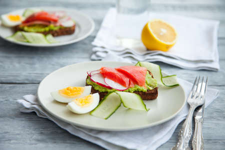Two smorrebroad sandwiches with red fish,Avocado,eggs and cucumber on plate on a table. Healthy breakfast or lunch. Imagens - 122411640