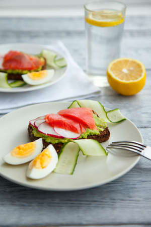Toast sandwich with Salmon, Avocado,eggs and cucumber on plate on a table. healthy easy food Imagens - 122411643