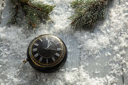 clock in the form of Christmas toys on a snowy background with spruce branches. The Concept Of Christmas. Christmas greeting card