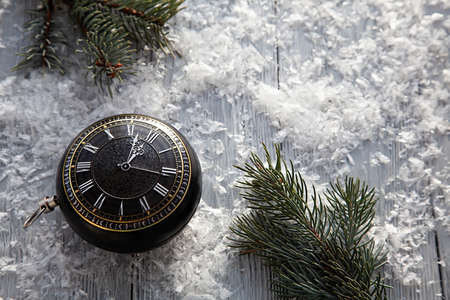 clock in the form of Christmas toys on a snowy background with spruce branches.Copy space. Christmas greeting card