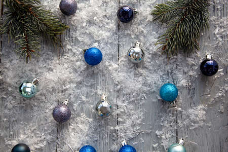Scattered Christmas toys on a gray snow-covered wooden table. The view from the top. Stok Fotoğraf