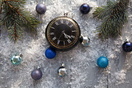 Scattered Christmas toys and clock on a gray snow-covered wooden table. The view from the top. Christmas background. Stock Photo
