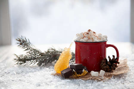 Christmas red cup with marshmallow on window.Snowy background.