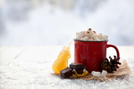 Christmas red cup with marshmallow on snowy background. Copy space Stock Photo