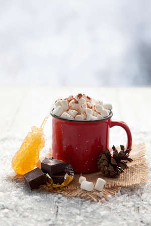 Christmas red cup with marshmallow on snowy background. Stock Photo