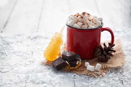 Christmas red cup with marshmallow on snowy background. Stok Fotoğraf