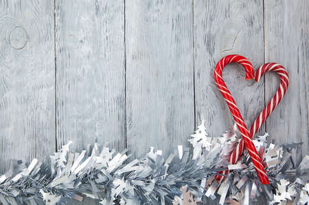 Christmas heart of two red lollipops on a wooden gray background with festive decoration. Christmas background, top view and copy space Stok Fotoğraf
