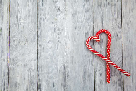 Christmas heart of two red lollipops on a wooden gray background. Christmas background, top view and copy space Stok Fotoğraf