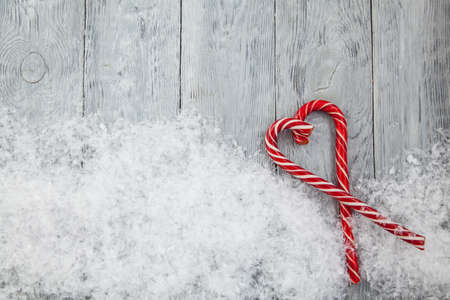 Christmas heart of two red lollipops on a wooden snowy gray background. Christmas background, top view and copy space Stok Fotoğraf