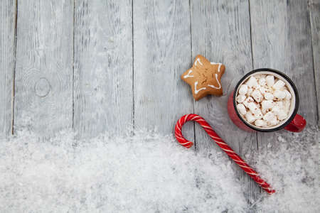 Christmas candy cane and gingerbread on snowy background top view .Greeting card on Christmas and New Year.