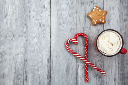 Red mag of drink with candy cane and Christmas gigerbread on wooden background. Copy space