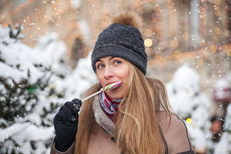 young woman dressed in winter clothes eating colorful Lollipop on Christmas snowy street Stok Fotoğraf