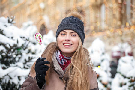 smiling young woman dressed in winter clothes eating colorful Lollipop on Christmas snowy street