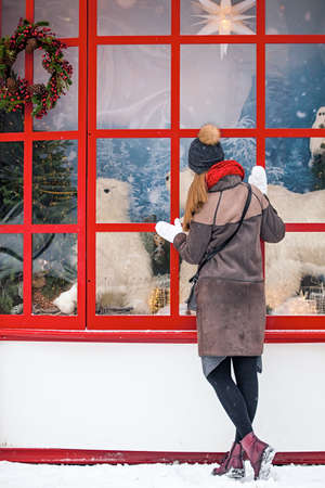 Young woman with gifts looks at a shop window on Christmas day. The concept of Christmas shopping