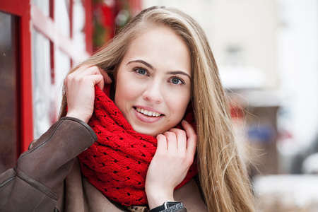 smiling young woman dressed in winter clothes on street