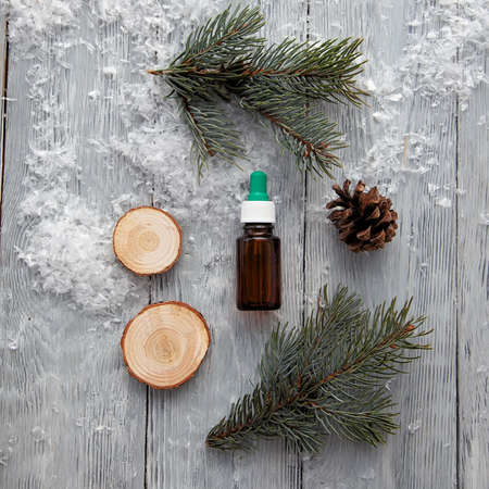 Pine aroma oil extract, cosmetic bottle aromatherapy on winter snowy background.