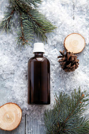 pine aroma oil extract natural in cosmetic bottle aromatherapy on winter snowy background