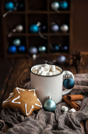 Cup of coffee with marshmallow, gingerbread on Christmas wooden background.