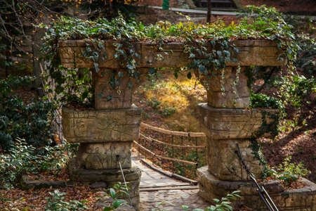Stone arch, entrance to a suspended wooden bridge. Summer fairy garden with a bridge.