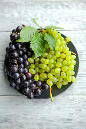 A cluster of white and red grapes on a round straw tray and grey wooden table
