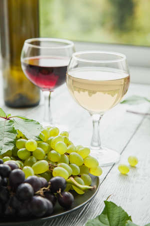 Two glasses with different varieties of wine and a plate with different ripe grapes. The concept of wine tasting