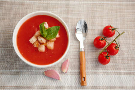 Tomato cream soup in a white bowl with a cherry tomatoes branch on the table. The view from the top. Italian soup.