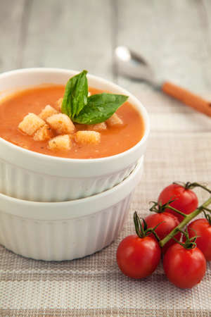 Tomato cream soup in a white bowl with a cherry tomatoes branch on the table. Italian soup.