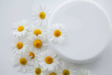 White jar of moisturizer and chamomile flowers on a white background. Stock fotó
