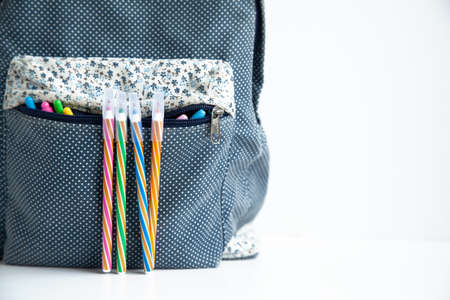School bag with colored pens on the white background Stock fotó