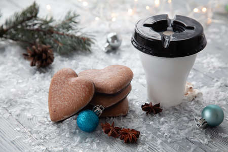 Cup of hot cocoa with marshmallows and Christmas gingerbread in the form of a heart on a snowy wooden background and window.