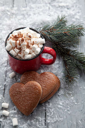Cup of hot cocoa with marshmallows and Christmas gingerbread in the form of a heart on a snowy wooden background.