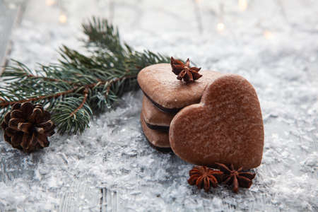 Christmas gingerbread in the form of a heart on a snowy wooden background Stock fotó