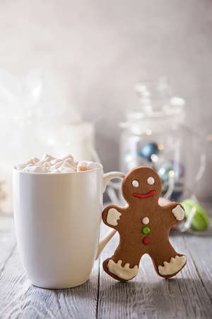 White mag of coffee with marshmallow and gingerbread snowman on a wooden table. Christmas break .