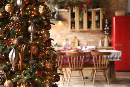 New years holiday interior. Home environment. Large Christmas tree with decor and kitchen in the background in defocus
