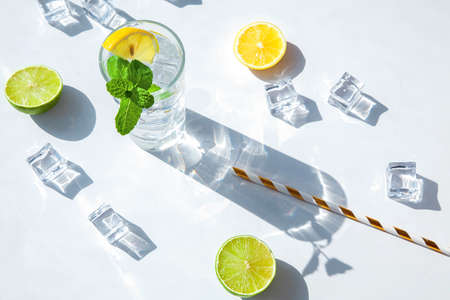 Lemon and mint cocktail or lemonade on a textured stone background, top view. A glass with a drink with a hard shadow from the sunlight. Summer composition. Stockfoto