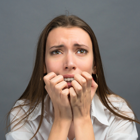 apprehensive: Frightened and stressed young business woman biting her fingers Stock Photo