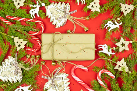 Gift in a craft paper, fir branches, christmas toys and decorations, candy canes on a red background. Top view Christmas composition over red background. Winter holidays, new year concept.
