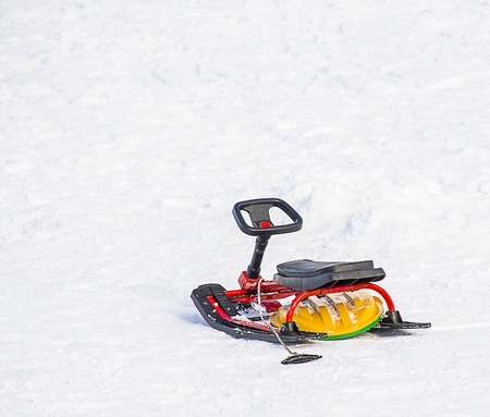 to steer a sledge: Children snow scooter (snowmobile toy) in the snow Stock Photo